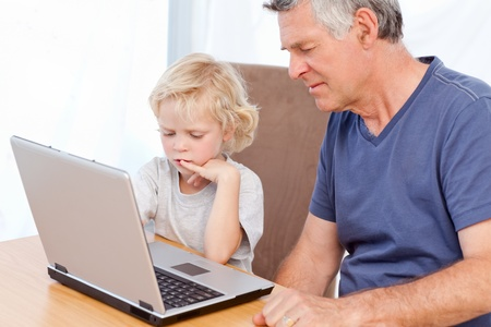Lovely boy and his grandfather looking at their laptop at home photo