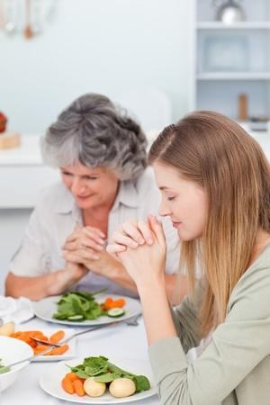 family praying: Familia rezando en la mesa