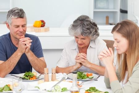 family praying: Adorable familia orando en la tabla