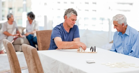 Seniors playing chess at home photo