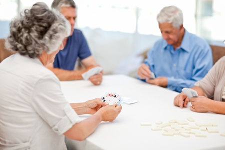 Retired people playing cards together at home photo