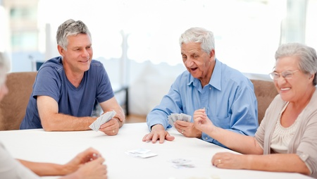 seniors homes: Retired people playing cards together at home