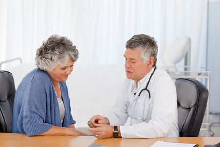 A senior doctor with his patient in his office photo