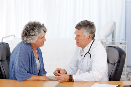 A senior doctor telling something to the patient in his office photo