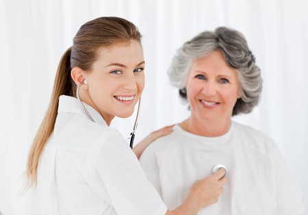 Nurse taking the blood pressure of her patient Stock Photo - 10206832