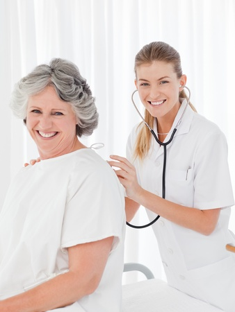 Pretty nurse taking the heartbeat of her patient photo