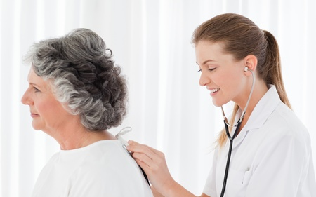Pretty nurse taking the heartbeat of her patient Stock Photo - 10212672