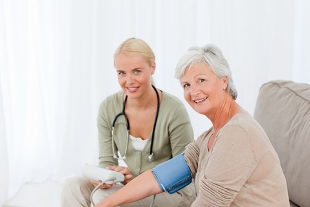 Lovely doctor taking the blood pressure of her patient Stock Photo - 10214865