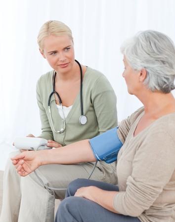 tomar medicina: Doctor encantadora tomar la presi�n arterial de su paciente