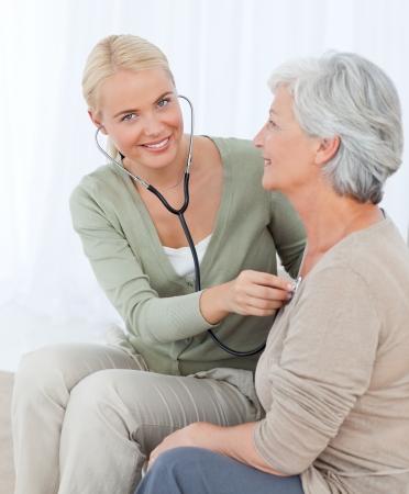 empleadas domesticas: Enfermera de tomar la heartbreat de su paciente en el hogar