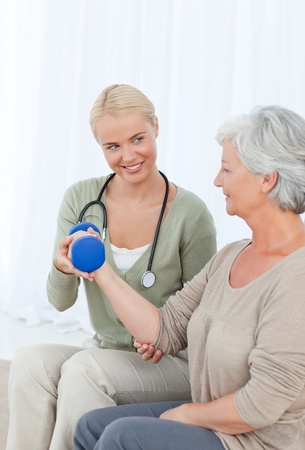 Beautiful nurse helping her patient to do exercises Stock Photo - 10217969