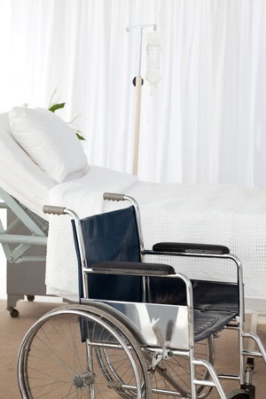 A wheelchair and a bed in the room photo