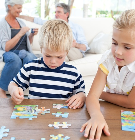 Children playing puzzle in the living room photo