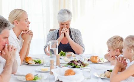 family praying: Linda familia rezando en la mesa