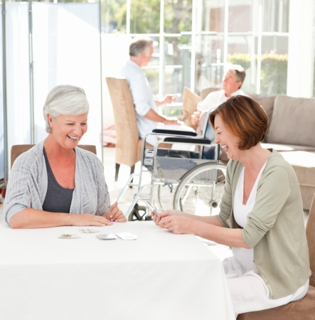 mujeres ancianas: Las mujeres mayores jugando a las cartas mientras sus maridos est�n hablando