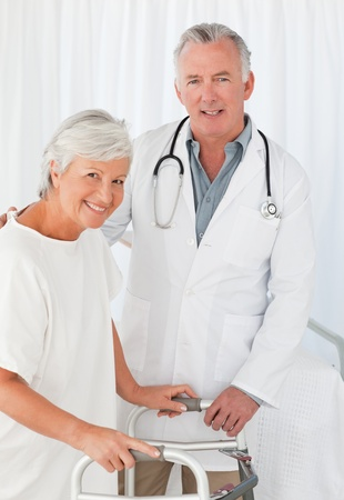 Doctor helping his patient to walk photo