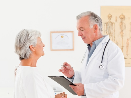 Senior doctor talking with his sick patient photo