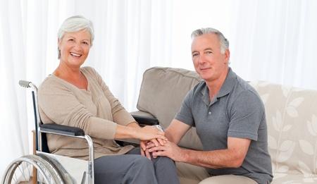 persona en silla de ruedas: Mujer con su marido en una silla de ruedas