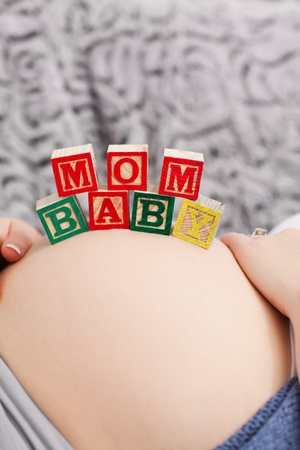 Pregnant young woman with cubes on her belly at home Stock Photo - 10218986
