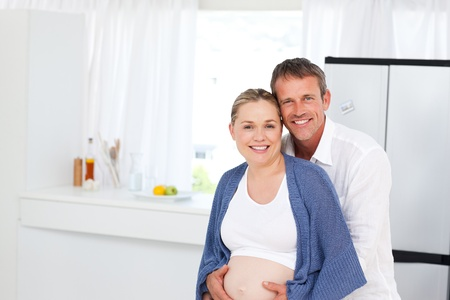 Couples hand on the belly of the pregnant woman photo