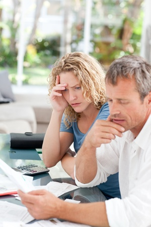Desperate couple calculating their domestic bills at home photo