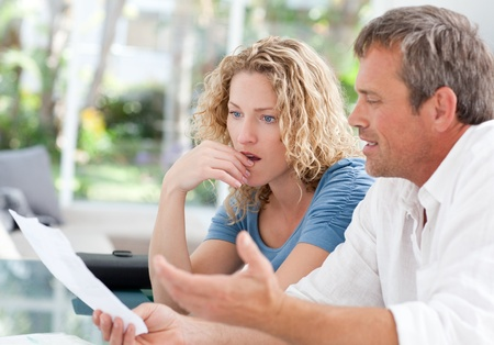 Desperate couple calculating their domestic bills at home Stock Photo - 10220130