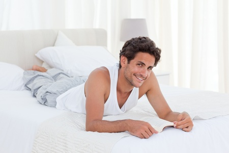 Man reading a book on his bed at home Stock Photo - 10215055
