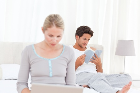 Woman working on her laptop while her husband is reading at home photo