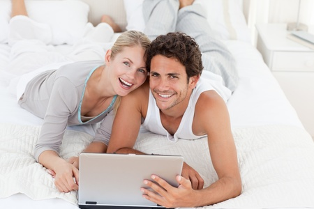 Young couple with the laptop in their bedroom photo