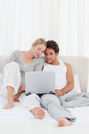 Adorable couple looking at their laptop on the bed at home photo