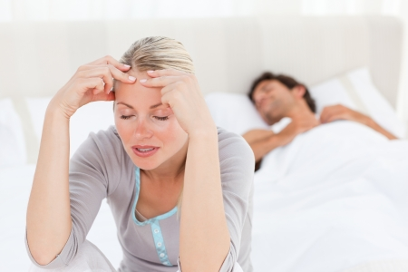 Attractive woman having a headache while her husband is sleeping at home photo