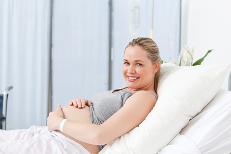 Pregnant young woman on a hospital bed photo