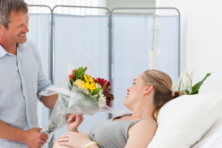 Man giving flowers to his pregnant wife photo