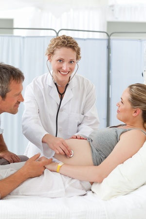 Pregnant woman with her husband listening to the nurse Stock Photo - 10218570