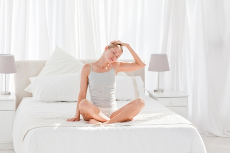Beautiful woman practicing yoga on her bed at home photo