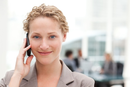 Beautiful businesswoman phoning in her office photo
