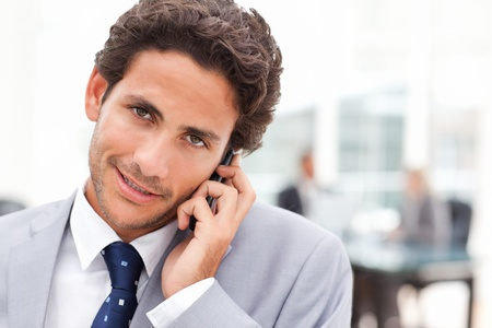 charismatic: Charming businessman phoning in his office Stock Photo