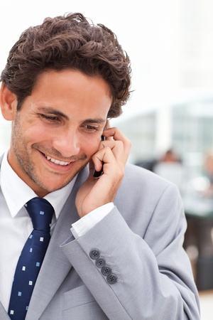 Charming businessman phoning in his office photo
