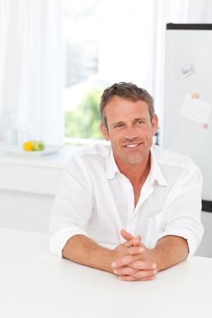 Handsome man sitting in his kitchen photo