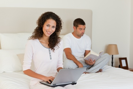 Woman working on her laptop while her husband is reading photo