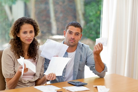 Young couple calculating their domestic bills at home Stock Photo - 10220365