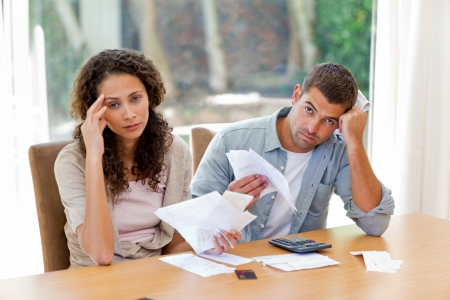 Young couple calculating their domestic bills at home photo