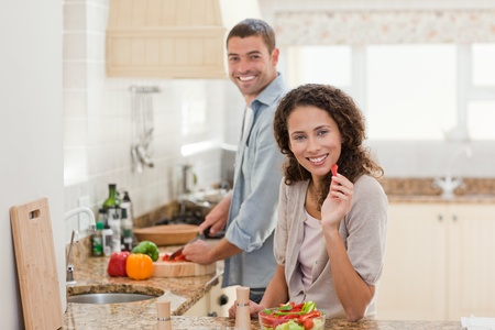 Beautiful woman looking at her husband who is cooking at home Stock Photo - 10219154