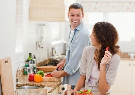 hombre cocinando: Hermosa mujer mirando a su marido que está cocinando en su casa Foto de archivo