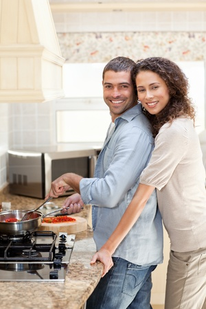 Woman hugging her husband while he is cooking at home photo