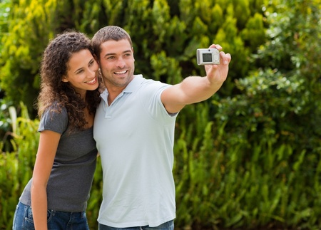 Lovely couple taking a picture of themselve in the garden photo