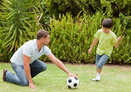 Son playing football with his father photo