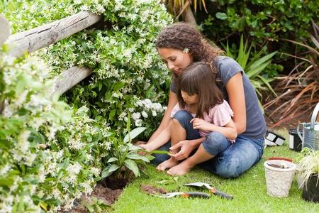 werkende moeder: Moeder en dochter werken in de tuin Stockfoto