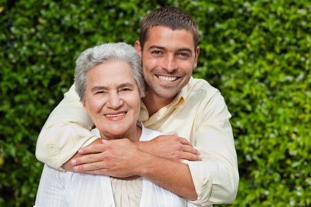 madre e hijo: El hombre abraza a su madre en el jard�n