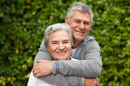 Elderly couple hugging in the garden photo